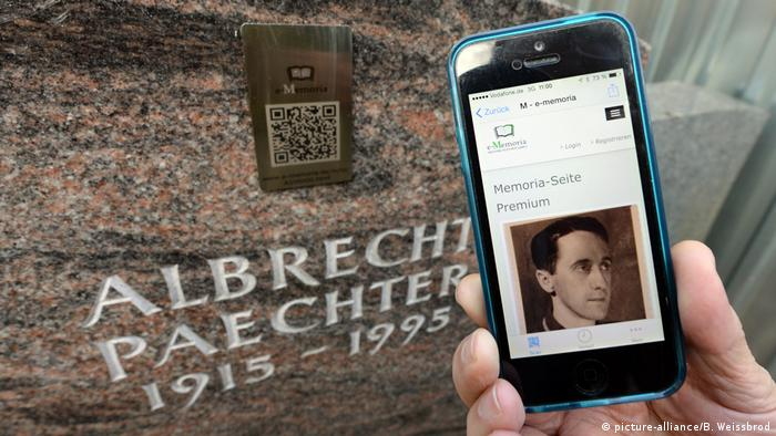 Person holding smartphone in front of gravestone