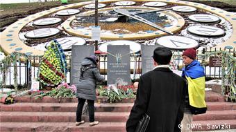 Женщина возлагает цветы к мемориалу Героям Небесной сотни