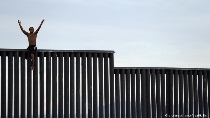 Sem camisa e de calças curtas, homem hondurenho está sentado no muro fronteiriço entre o México e os EUA em Tijuana, no México. Seus braços estão levantados. O muro é uma série de pilastras, sem concreto contínuo.