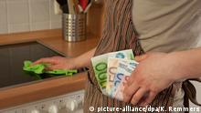 ILLUSTRATION - Eine Frau steckt am 12.02.2012 in Hannover Geldscheine in ihre Schürze. | Verwendung weltweit