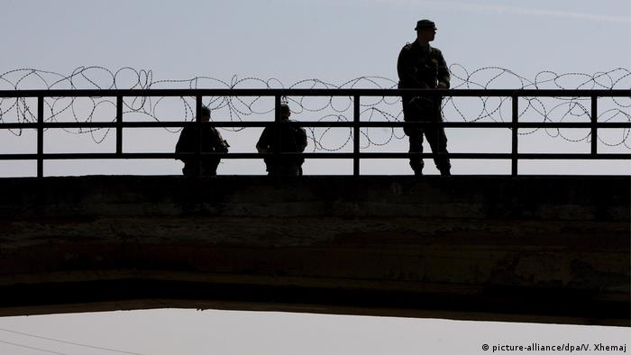 NATO soldiers stand guard between Kosovo's border with Serbia