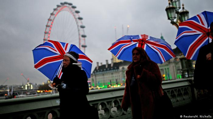 People walk under Union flag themed umbrellas on Westminster Bridge in London