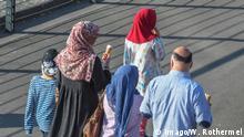 Eine Migrantenfamilie geht spazieren an der Rheinuferpromenade in Düsseldorf ( Nordrhein-Westfalen). Wenn die Sonne scheint, zieht es Einheimische wie Touristen an die direkt am Rhein gelegenen, Fussgängern vorbehaltenen Promenade. Foto:Winfried Rothermel a Migrant family is walk to the Rhine promenade in Dusseldorf North Rhine Westphalia if the Sun seems shoots it Locals like Tourists to the directly at Rhine located Pedestrians reserved Promenade Photo Winfried Rothermel