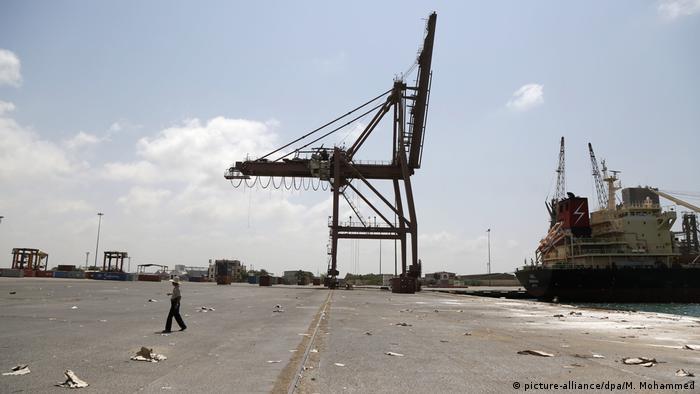 A man walks across the deserted Yemeni port of Hodeida