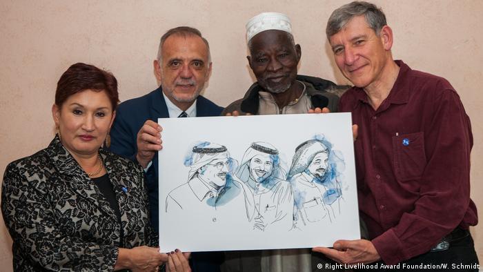 Right Livelihood Award laureates Thelma Aldana, Tony Rinaudo, Yacouba Sawadogo and Iván Velásquez hold up a picture of the three jailed laureates from Saudi Arabia, Abdullah Al-Hamid, Waleed Abu Al-Khair and Mohammad Fahad Al-Qahtani