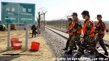DORASAN, SOUTH KOREA: South Korean de-mining troops walk across a railway after a metal gate of the barbed-wire-topped border fense, which divides the Korean peninsula, opens near Dorasan Station, 56km north of Seoul, 18 September, 2002. South and North Korea held ground-breaking ceremonies to rid landmines from the border for road and rail links.AFP PHOTO/KIM Jae-Hwan (Photo credit should read KIM JAE-HWAN/AFP/Getty Images)