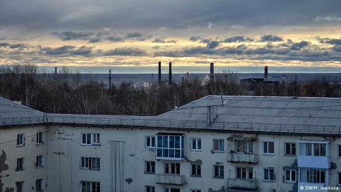 Smokestacks are seen on the horizon behind a building facade in Severouralsk, Russia