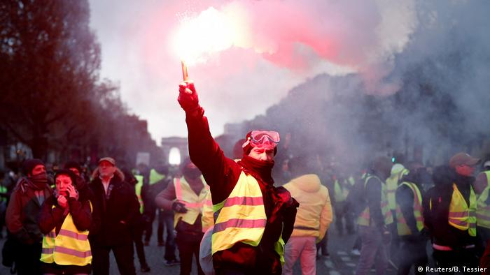 A yellow-vest protester holds up a flare on the Champs-Elysees (Reuters/B. Tessier)