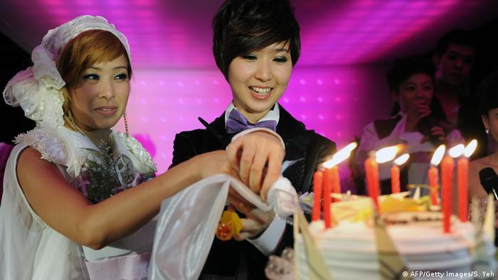 A same sex couple cut a cake during a mass wedding party