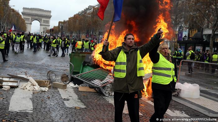 Protesters on the Champs-Elysees in Paris, with a burning barricade