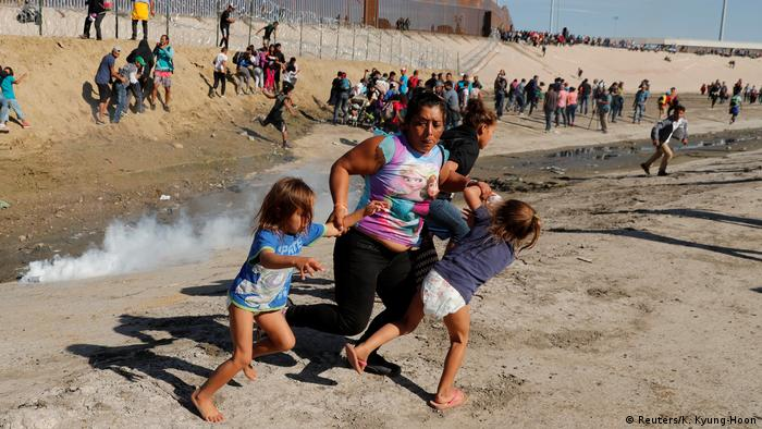 A migrant family, part of a caravan of thousands traveling from Central America en route to the United States, run away from tear gas