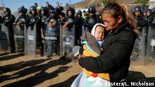 25.11.02018 *** Rosa Villa, 30, and her five-month-old son Esteban from Honduras, part of a caravan of thousands traveling from Central America en route to the United States, are pushed back from the border wall between the U.S and Mexico by Mexican police in Tijuana, Mexico November 25, 2018. REUTERS/Lucy Nicholson TPX IMAGES OF THE DAY