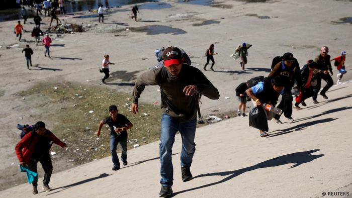 Migrants, part of a caravan of thousands traveling from Central America en route to the United States, run across the Tijuana river