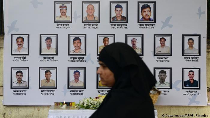 A woman in front of a poster of victims of the attack