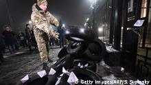 A protester throws down a tire to set a fire in front of the Russian Embassy in Kiev late on November 25, 2018, during a protest following an incident in the Black Sea off Moscow-annexed Crimea, in which three Ukrainian naval vessels were seized by a Russian border guard vessel, as the three ships were on their way through the Kerch Strait heading for the port of Mariupol. - Russia said on November 25 that it has seized three Ukrainian naval ships by force in a strait near Moscow-annexed Crimea, sparking alarm among Kiev's Western allies and raising fears of military escalation. Ukraine's navy had accused Russia of the unprecedented incident including firing on its vessels in the Kerch Strait, a narrow waterway that gives access to the Sea of Azov that is used by Ukraine and Russia. (Photo by SERGEI SUPINSKY / AFP) (Photo credit should read SERGEI SUPINSKY/AFP/Getty Images)