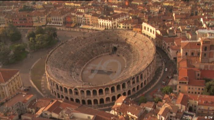 an ancient Colosseum with a signature in the middle (DW)