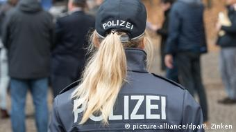 A police office with a ponytail stands with her back to the camera (picture-alliance/dpa/P. Zinken)