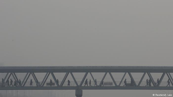 People walk across a bridge in a thick blanket of smog