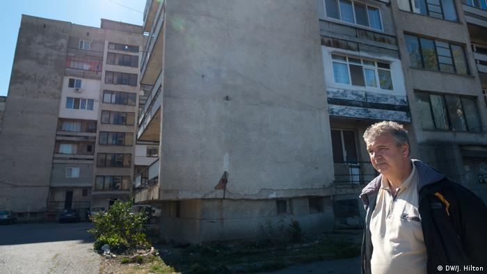 A man standing in front of a block of flats (DW/J. Hilton)