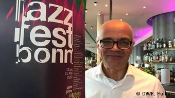 Peter Materna leans against a post in a hotel that has the jazzfest poster on it (DW/R. Fulker)