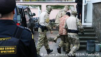 Сотрудники ФСБ ведут в здание суда в Симферополе задержанного украинского моряка, 27 ноября