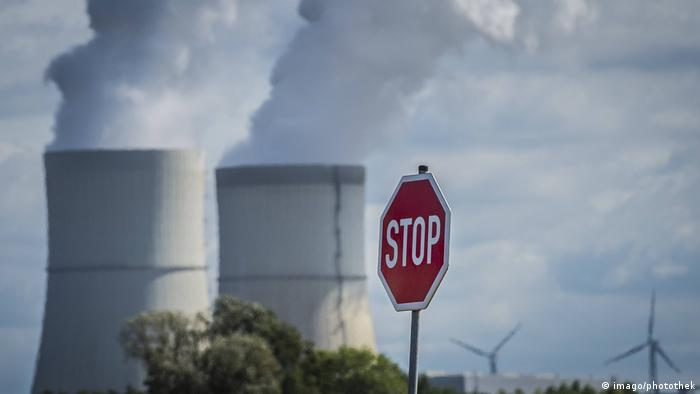 A stop sign stands in front of a coal-fired power plant, and wind turbines can be seen in the distance (imago/photothek)