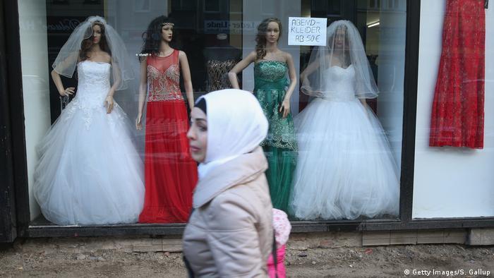 صورة رمزية لسيدة مسلمة في برلين تمر من أمام متجر لبيع فساتين الأعراس