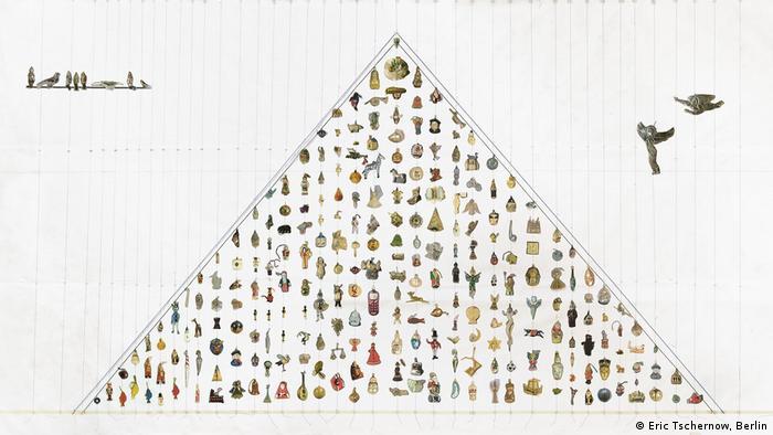 Man sieht ein dem Umriss des Weihnachtsbaums nachempfundenes Dreieck mit kleinen Männchen und Figuren, die aus anderen Kulturen kommen, wie zum Beispiel der chinesische Weihnachtsmann und der indonesische Schneemann (Eric Tschernow, Berlin)