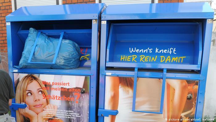 Zwei Altkleidercontainer stehen nebeneinander beschriftet u.a. mit lustigen Sprüchen wie Wenn's kneift, hier rein damit