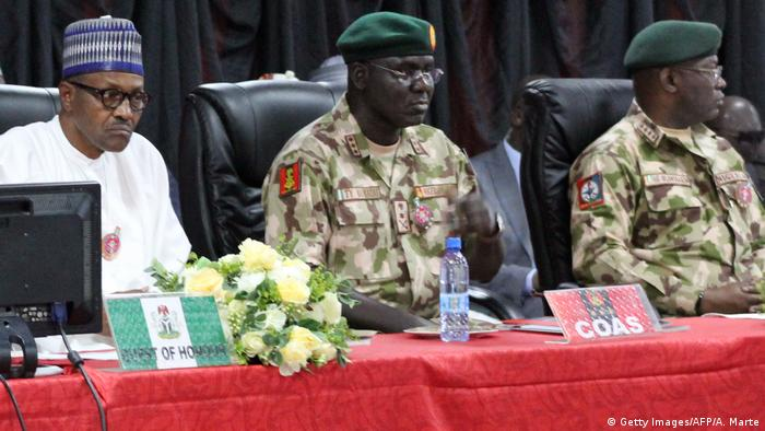 Nigerian President Muhammadu Buhari flanked by military officers