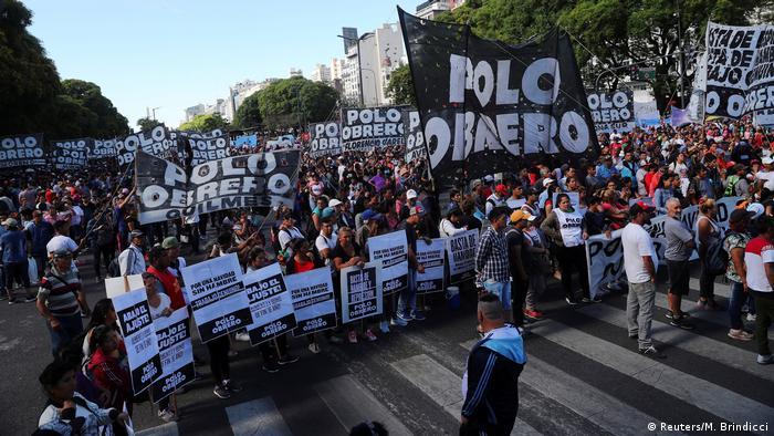 Militantes seguram faixas e cartazes em protesto contra realização da cúpula do G20