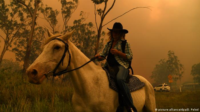 Woman on horse fleeing bushfires (picture-alliance/dpa/D. Peled)