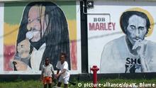 ARCHIV - Zwei Kinder gehen am 24.09.2002 im Stadtteil Tivoli-Gardens in Kingston (Jamaika) an Plakaten vorbei, die die Reggae-Legende Bob Marley zeigen. Foto: Klaus Blume/dpa (zu dpa Der missverstandene Prophet: Bob Marley wäre 70 geworden vom 31.01.2015) +++(c) dpa - Bildfunk+++ | Verwendung weltweit
