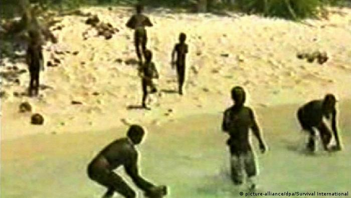 The image shows a group of tribal people in the North Sentinel island in the Andaman and Nicobar archipelago
