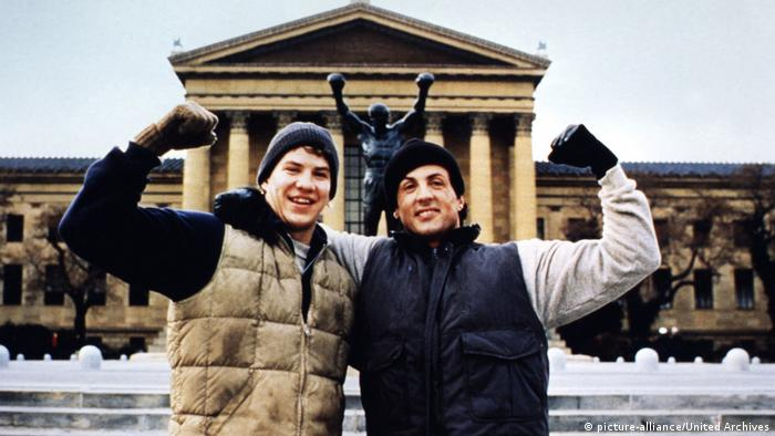 Sylvester Stallone vor einer Statue in Siegerpose (picture-alliance/United Archives)