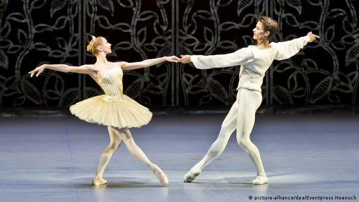 Two ballet dancers hold hands as they dance in the nutcracker