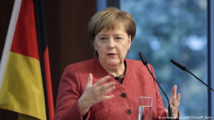 Merkel gesturing during a speech with the German flag behind her (picture-alliance/AP Photo/M. Sohn)