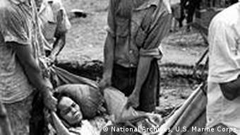 A wounded woman is carried by soldiers
