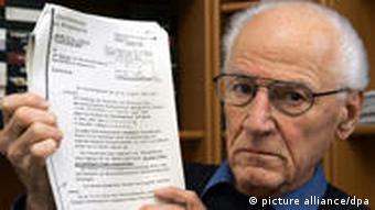 Ludwig Baumann holding up a document