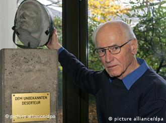 Baumann next to small stone memorial