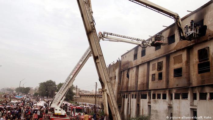 Cranes lift investigators to upper floor of a burned out factory