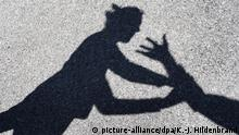 A shadow image of a man and woman fighting (picture-alliance/dpa/K.-J. Hildenbrand)