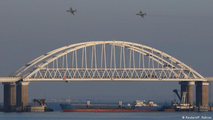 Russian jet fighters fly over a bridge connecting the Russian mainland with the Crimean Peninsula with a cargo ship beneath it after three Ukrainian navy vessels were stopped by Russia from entering the Sea of Azov. (Reuters/P. Rebrov)