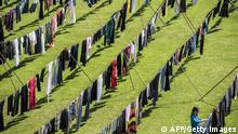 Alketa Xhafa Mripa hangs dresses on clotheslines at the Pristina stadium as part of her installation titled Thinking of You (AFP/Getty Images)