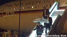 dpatopbilder - 29.11.2018, Nordrhein-Westfalen, Köln: Bundeskanzlerin Angela Merkel (CDU) verlässt mit einem Regenschirm in der Hand auf dem Rollfeld des Flughafens in Köln den Kanzler-Airbus «Konrad Adenauer». Wegen eines technischen Defekts am Flugzeug hat Merkel ihren Flug von Berlin zum G20-Gipfel in Buenos Aires am Donnerstagabend unterbrechen müssen. Die Maschine vom Typ A340-300 mit Merkel an Bord war um 19.00 Uhr in Berlin gestartet, sie landete gegen 21.00 Uhr in Köln. (RECROP - Bestmögliche Bildqualität) Foto: Jörg Blank/dpa | Verwendung weltweit
