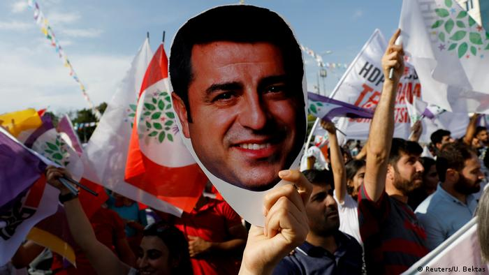 A supporter of the pro-Kurdish Peoples' Democratic Party (HDP) holds a mask of their jailed former leader and presidential candidate Selahattin Demirtas (Reuters/U. Bektas)