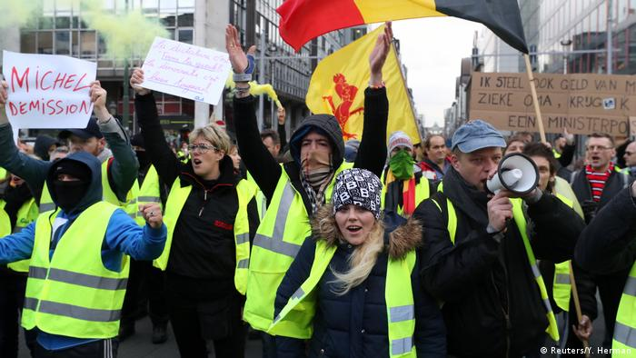 Protesters wearing holding placards calling for the resignation of Belgian Prime Minister Charles Michel