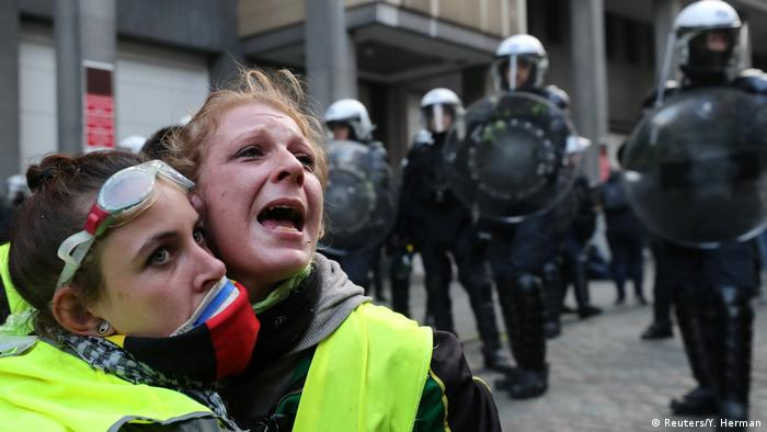 Two protesters in yellow vests cling to one another and cry out as police stand in the background (Reuters/Y. Herman)
