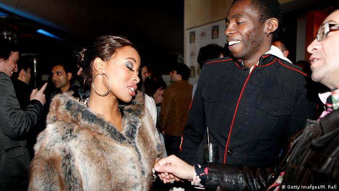 Khanyi Mbau in a fur coat and hooped earrings talks to two men (Getty Imafges/M. Rall)