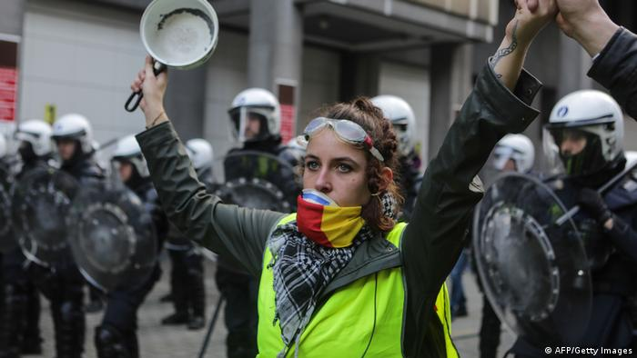 Yellow vest protester holds up a saucepan during a demonstration